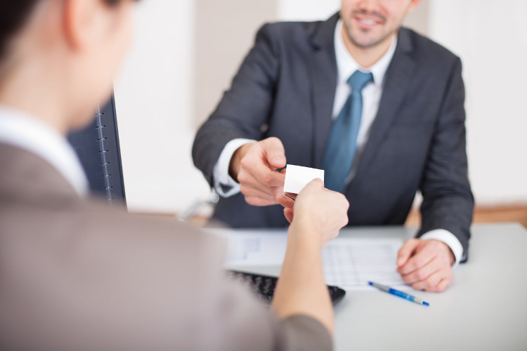 Candidate giving business card to employer