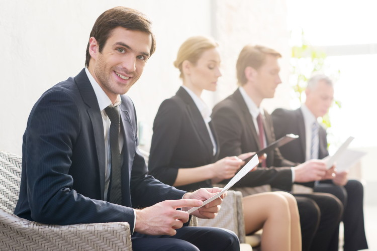 Confident candidate smiles while waiting for job interview