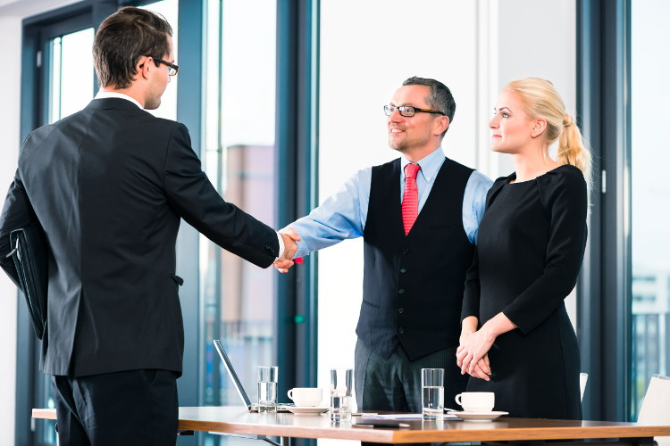 Job candidate shakes hands with employers