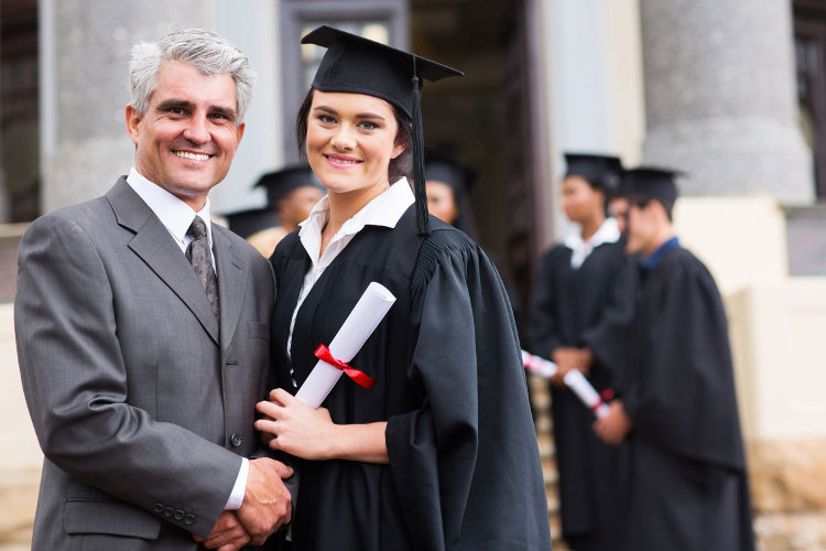 College graduate standing with her father