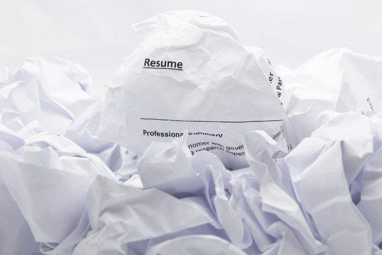 Crumpled up resume on a pile of paper trash